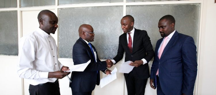 (on the left) General Secretary UCA shakes hand with Moses Mugisha from Puliida after the signing the MOU